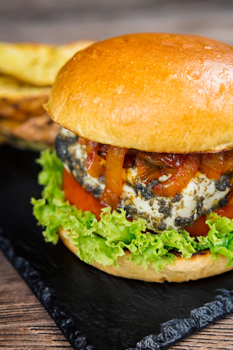 Portrait image of a Halloumi burger featuring frisee lettuce, a slice of tomato and spiced onions served on a slate