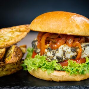 Square image of a Halloumi burger featuring frisee lettuce, a slice of tomato and spiced onions served on a slate