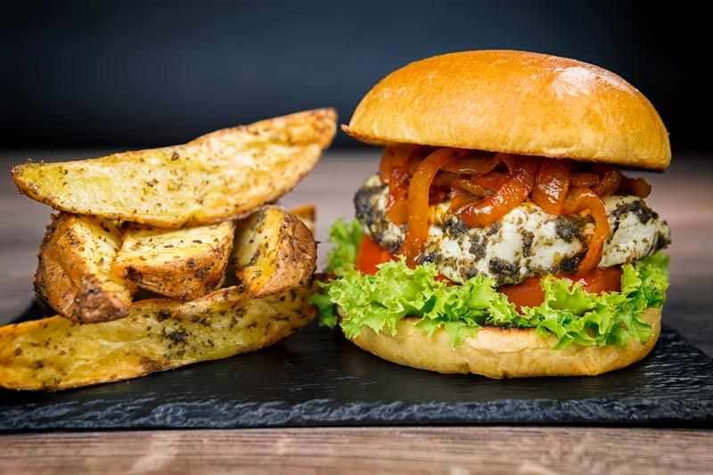 Portrait image of a Halloumi burger featuring frisee lettuce, a slice of tomato and spiced onions served on a slate with potato wedges