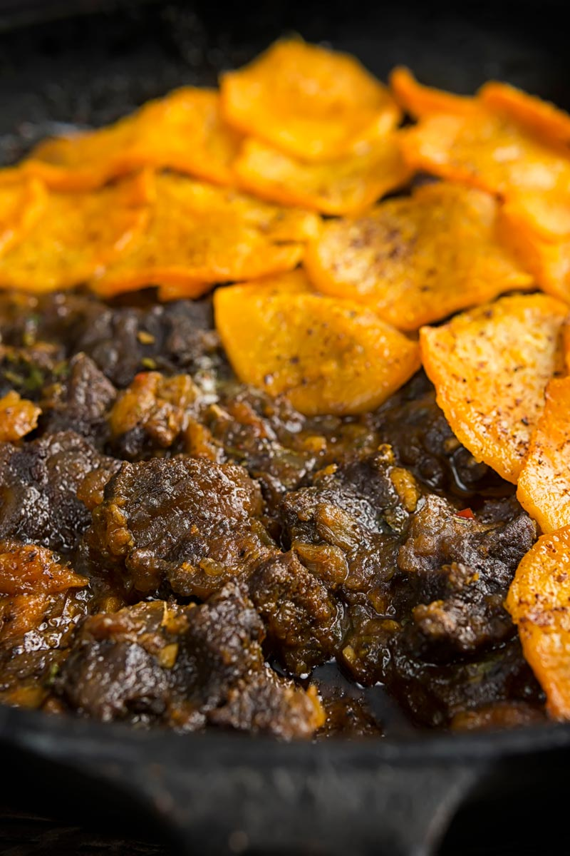 Portrait close up image of a beef hotpot served in a cast iron skillet with a sliced sweet potato topping