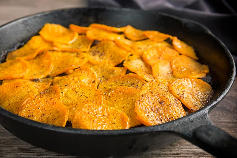 Landscape image of a beef hotpot served in a cast iron skillet with a sliced sweet potato topping