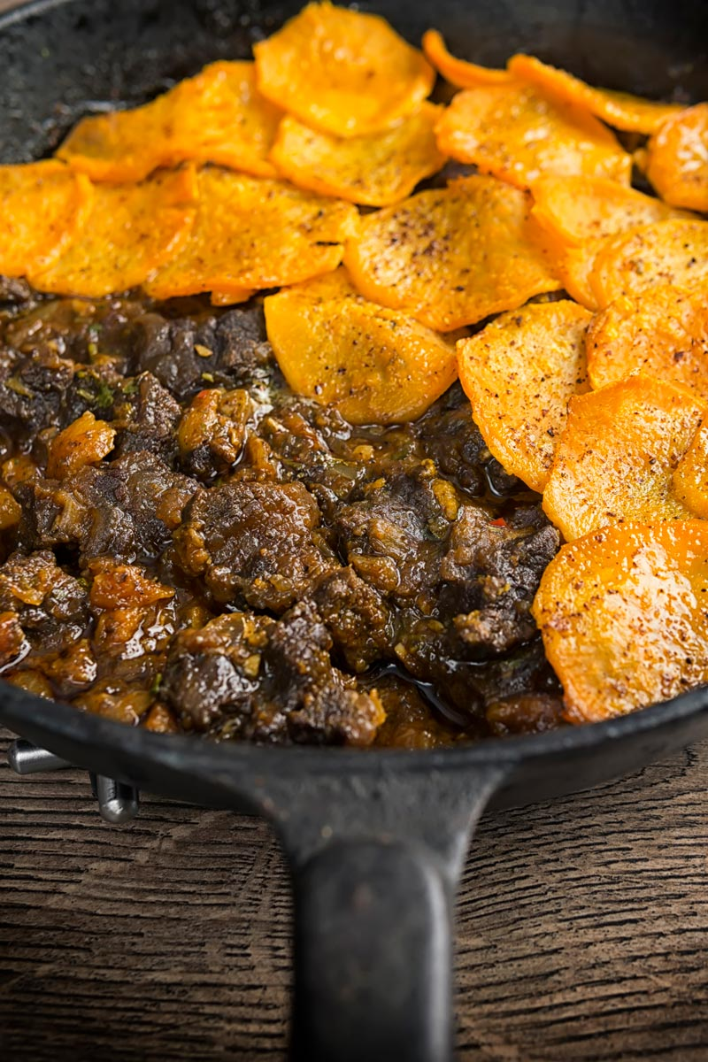 Portrait image of a beef hotpot served in a cast iron skillet with a sliced sweet potato topping
