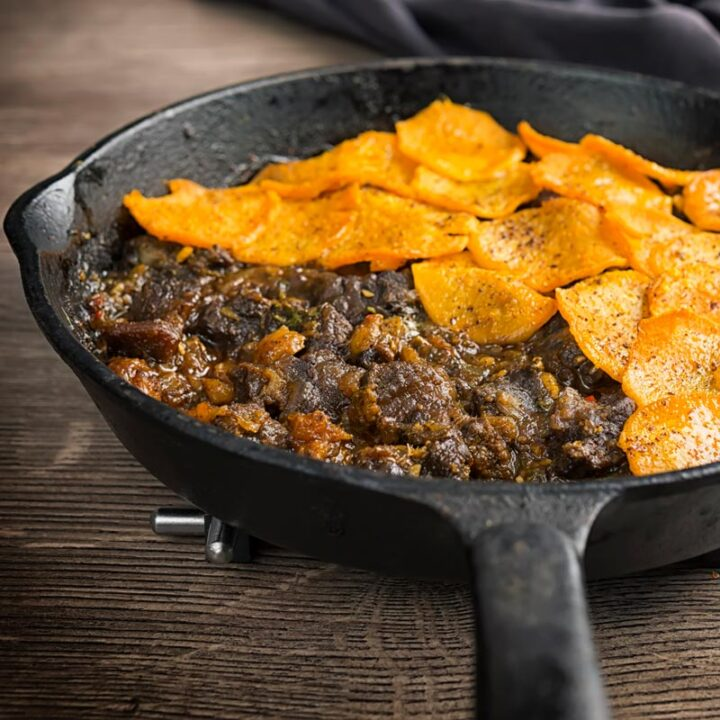 Square image of a beef hotpot served in a cast iron skillet with a sliced sweet potato topping