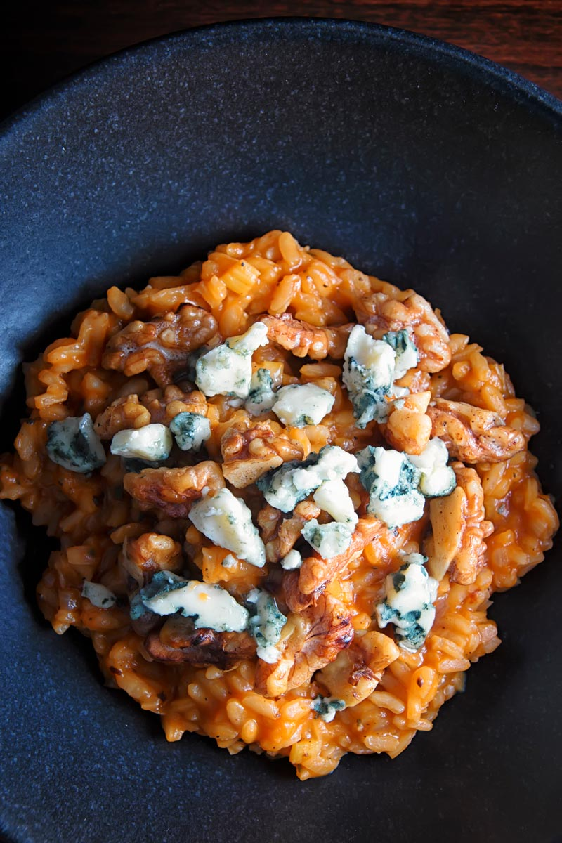 Portrait overhead image of a pureed pumpkin risotto with blue cheese and walnuts served in a black bowl