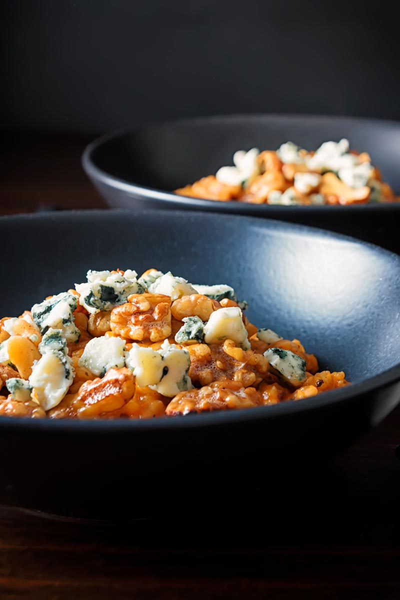 Portrait image of a pureed pumpkin risotto with blue cheese and walnuts served in two black bowls