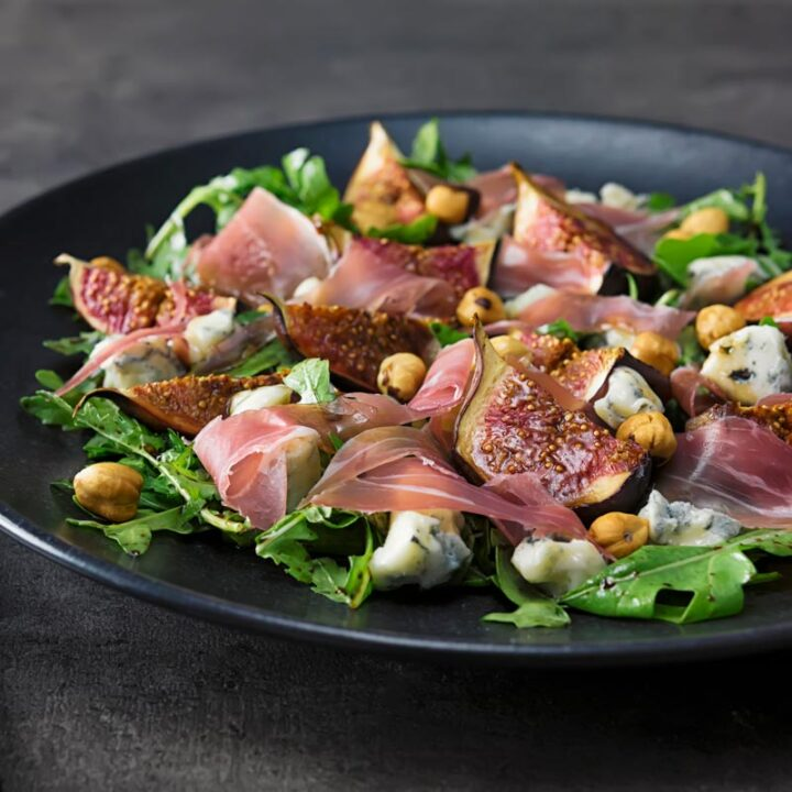 Square image of a roasted fig salad paired with blue cheese , rocket, Prosciutto Ham and hazelnuts served on a black plate