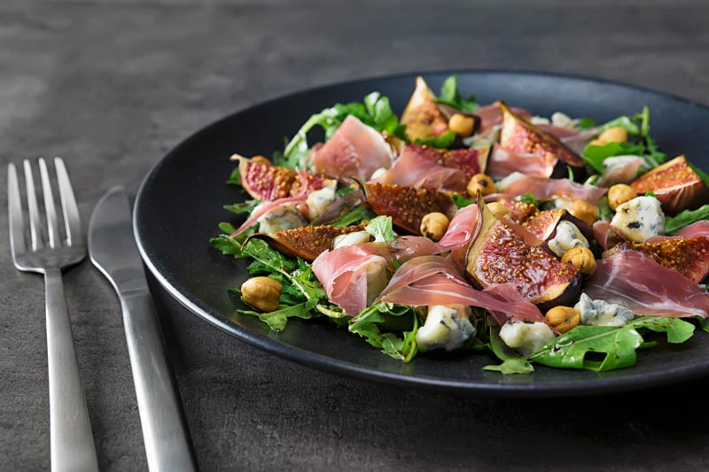 Landscape image of a roasted fig salad paired with blue cheese, rocket, Prosciutto Ham and hazelnuts served on a black plate