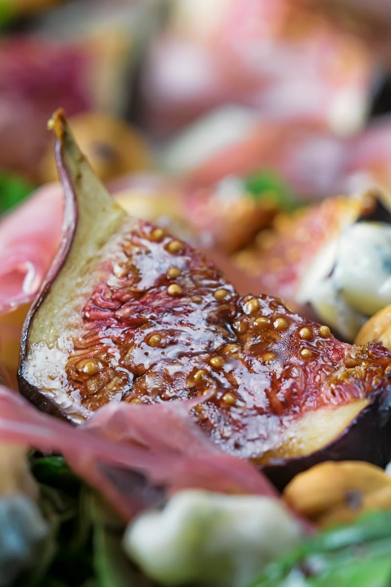 Portrait closeup image of a roasted fig in a salad with out of focus ham and hazelnuts