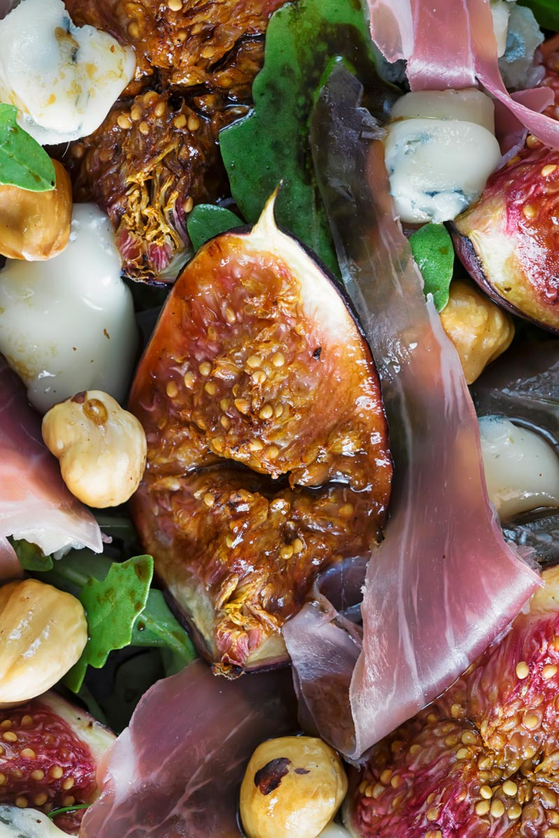 Portrait closeup overhead image of a roasted fig salad paired with blue cheese, rocket, Prosciutto Ham and hazelnuts