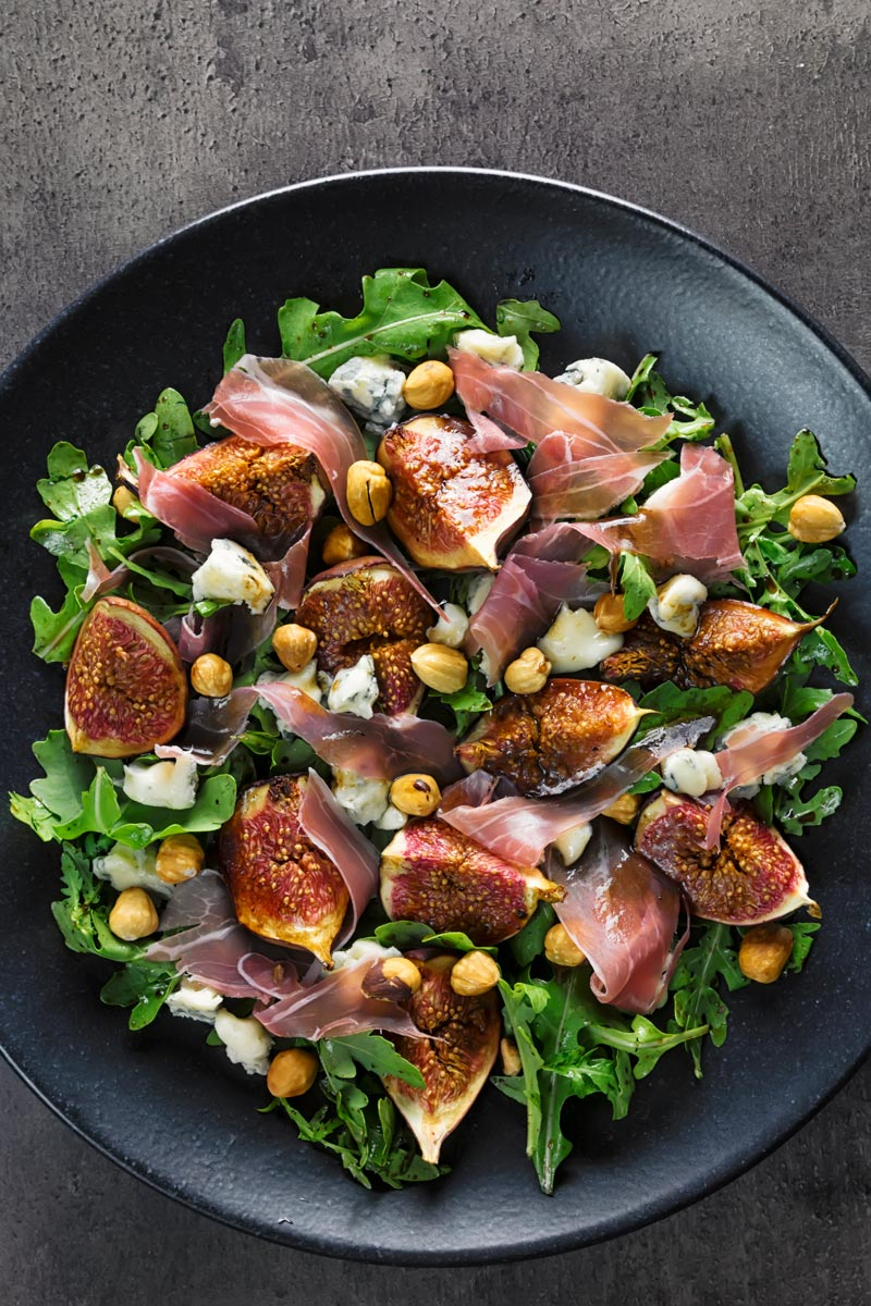 Portrait overhead image of a roasted fig salad paired with blue cheese, rocket, Prosciutto Ham and hazelnuts served on a black plate