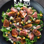 Portrait overhead image of a roasted fig salad paired with blue cheese, rocket, Prosciutto Ham and hazelnuts served on a black plate with text overlay