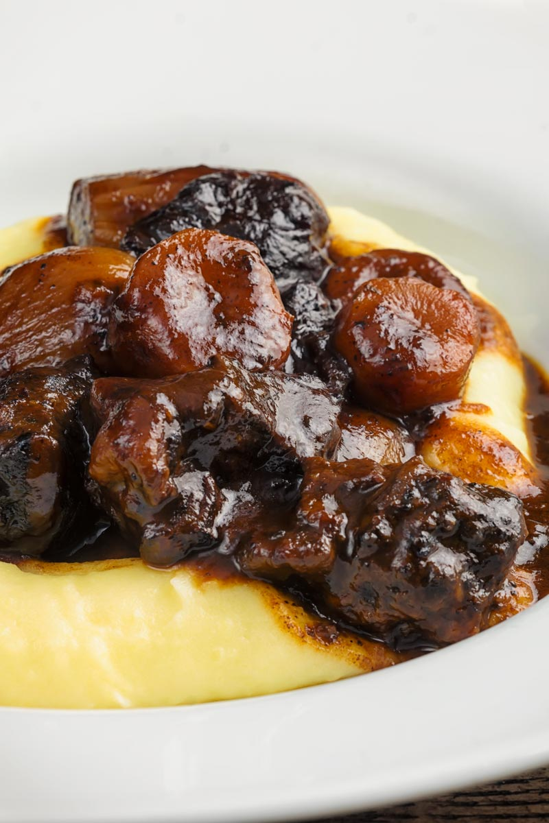 Close up portrait image of a daube of beef stew on a bed of creamy mashed potato served in a shallow white bowl