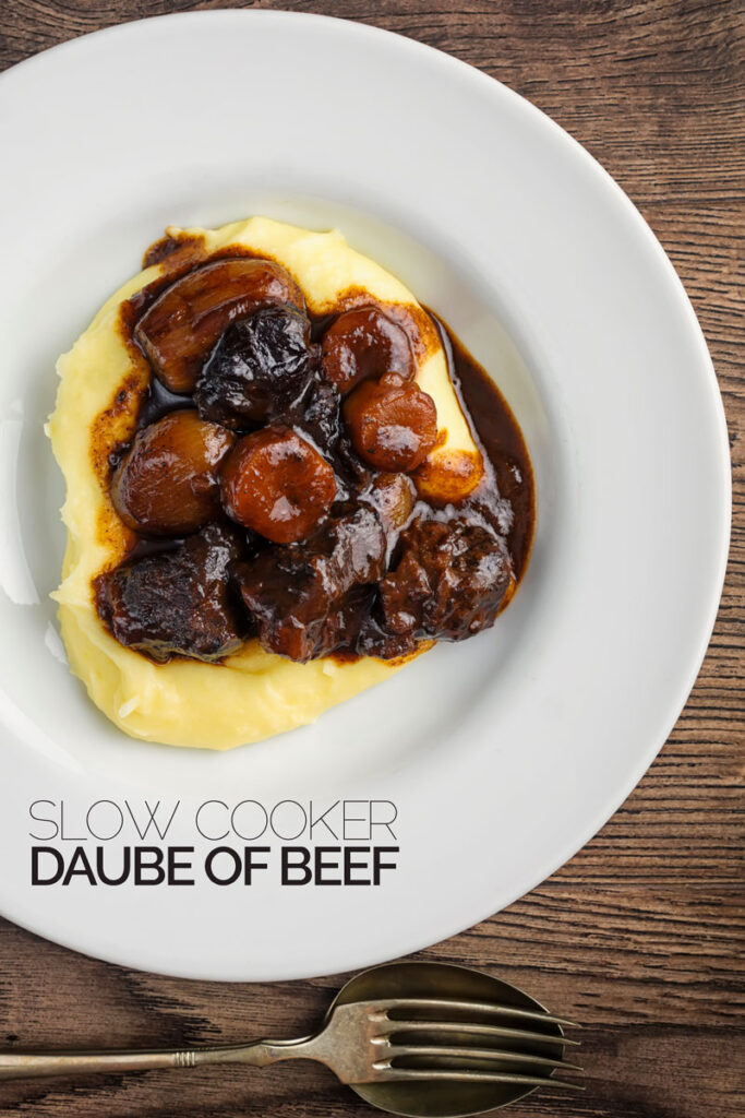Overhead portrait image of a daube of beef stew on a bed of creamy mashed potato served in a shallow white bowl with text overlay