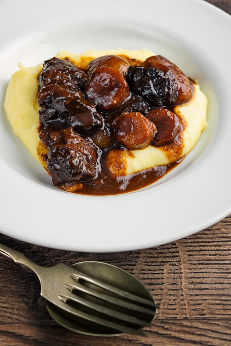 Portrait image of a daube of beef stew on a bed of creamy mashed potato served in a shallow white bowl