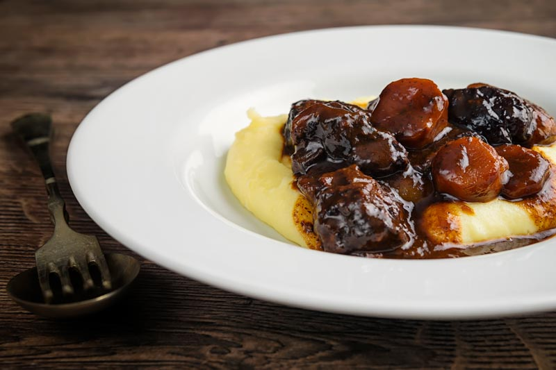 Landscape image of a daube of beef stew on a bed of creamy mashed potato served in a shallow white bowl