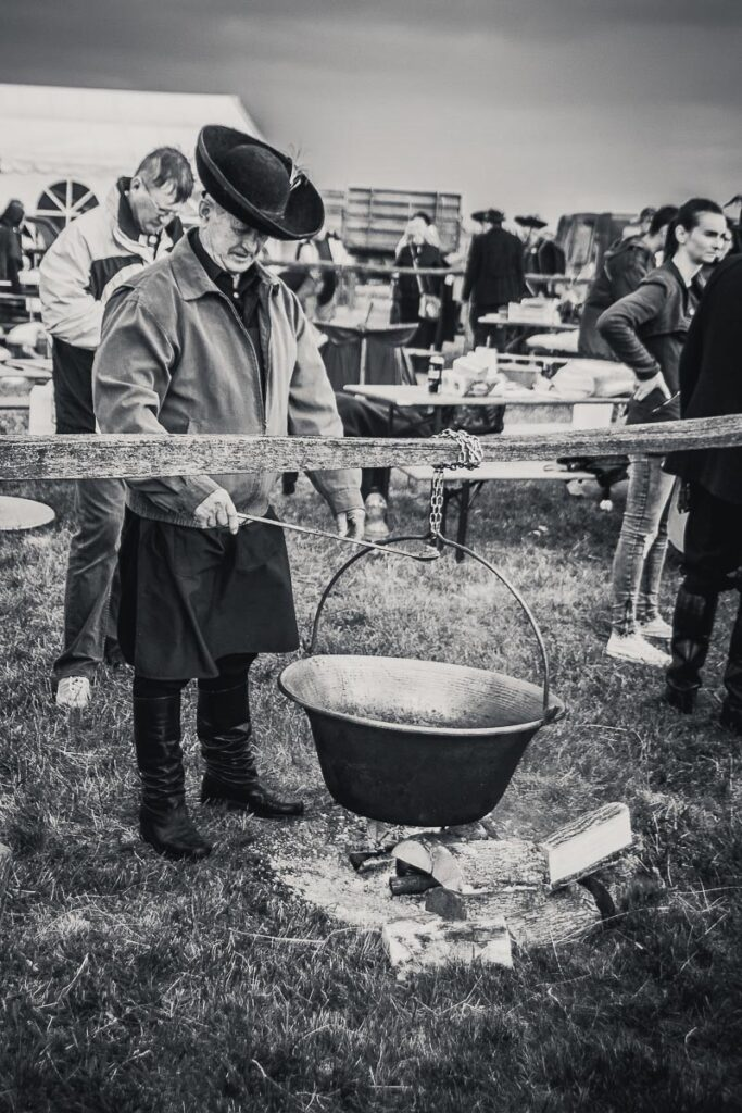 Black and white image of traditional hungarian cooking over an open fire