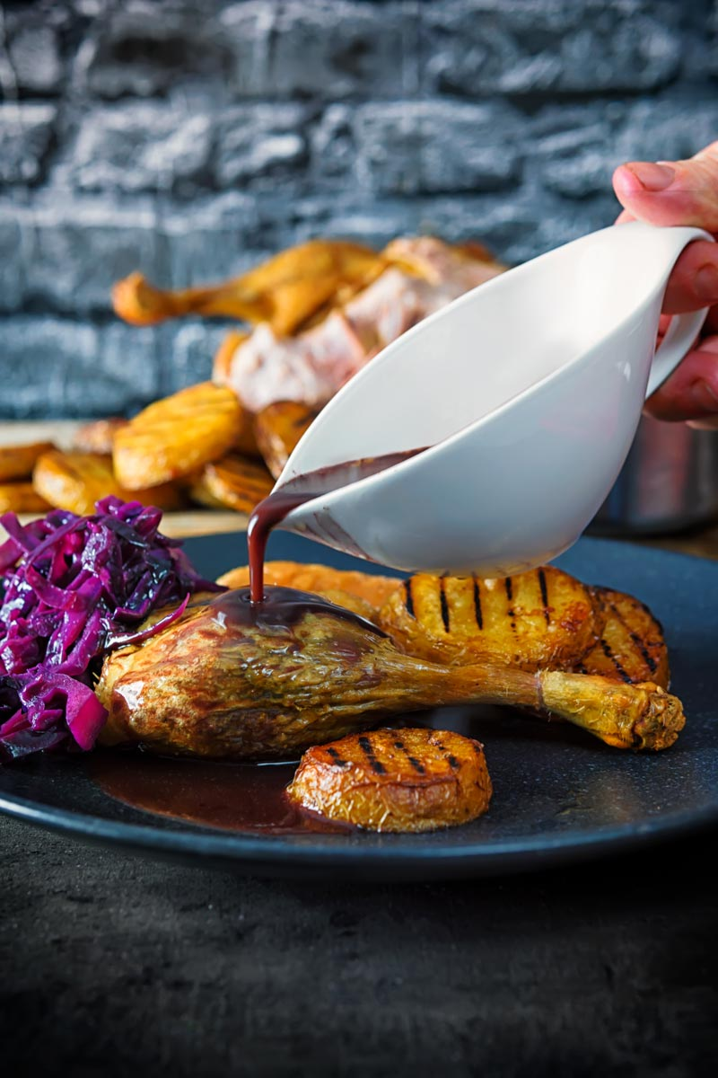 Portrait image of a red wine gravy being poured over a roast duck leg served with roasted scalloped potatoes and red cabbage