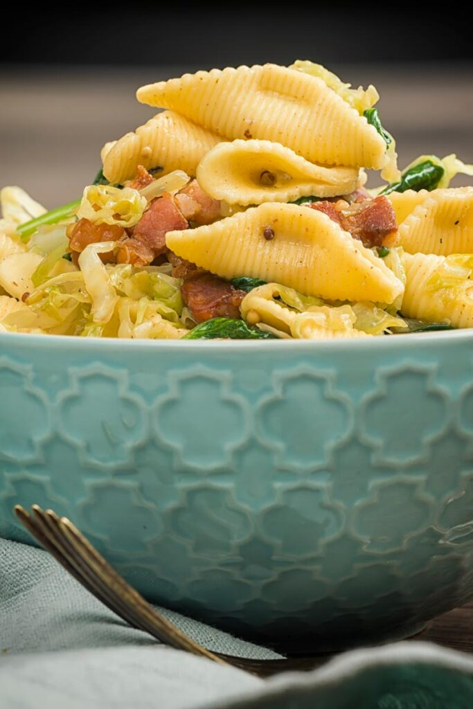 Portrait image of cabbage and bacon pasta served in a baby blue bowl