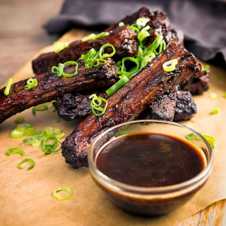 Square image of a pile of sticky Chinese Spare Ribs served on a board with spring onions and a dipping sauce