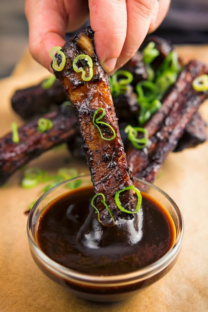 Portrait image of sticky Instant Pot Chinese spare ribs being dipped into a sauce