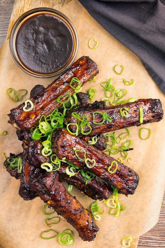 Portrait overhead image of a pile of sticky Chinese Spare Ribs served on a board with spring onions and a dipping sauce