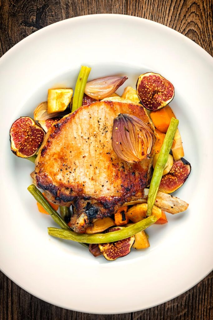 Portrait overhead image of a pork chop tray bake featuring fresh figs, green beans, shallots, carrots and parsnips serve in a white shallow bowl