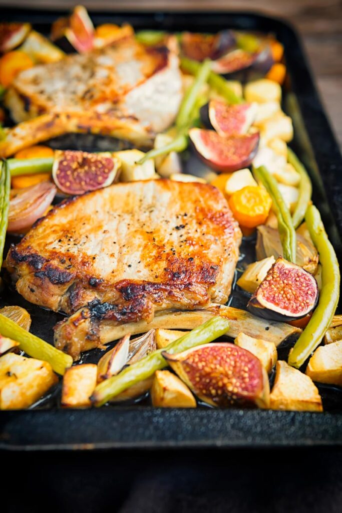Portrait image of a pork chop tray bake featuring fresh figs, green beans, shallots, carrots and parsnips