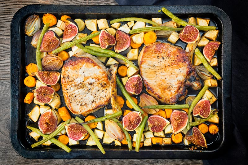 Landscape overhead image of a pork chop tray bake featuring fresh figs, green beans, shallots, carrots and parsnips