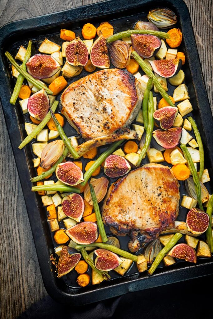 Portrait overhead image of a pork chop tray bake featuring fresh figs, green beans, shallots, carrots and parsnips