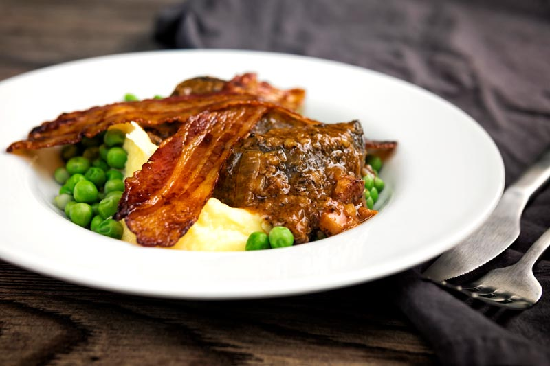 Landscape image of bacon liver an onions with mash and peas served in a white bowl with text overlay