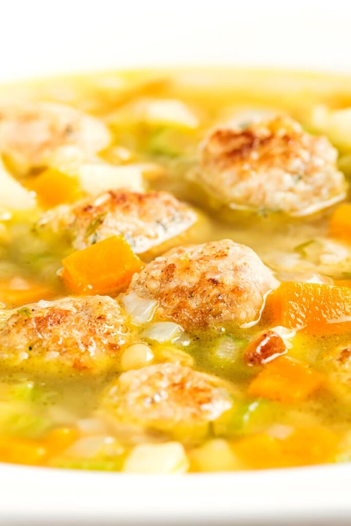Portrait close up image of a simple meatball soup with diced vegetables and pork meatballs and a light broth in a white bowl