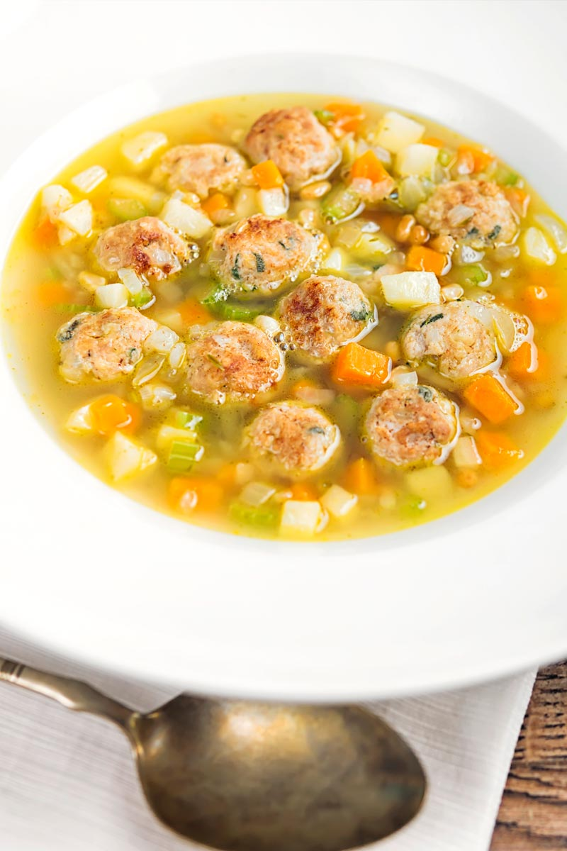 Portrait image of a simple meatball soup with diced vegetables and pork meatballs and a light broth in a white bowl