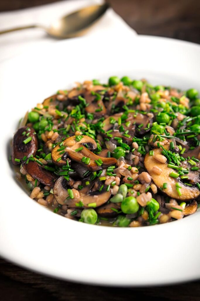 Portrait image of a pea and mushroom orzotto featuring pearl barley served in a white shallow bowl