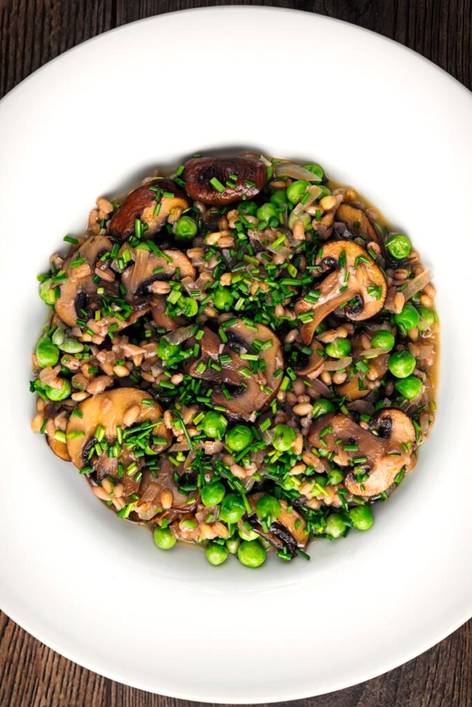 Portrait overhead image of a pea and mushroom orzotto featuring pearl barley served in a white shallow bowl