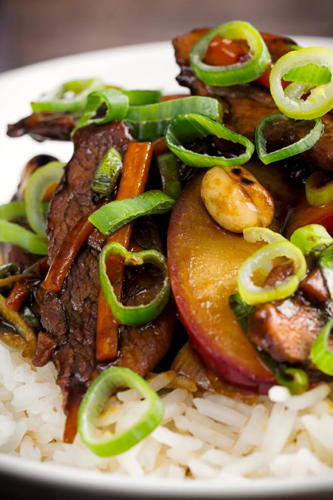 Portrait close up image of a stir fried duck with plums, spring onions and carrots served with white rice