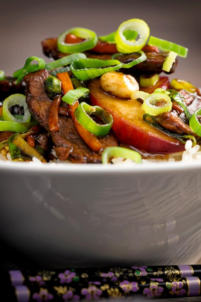 Portrait image of a duck stir fry with plums, spring onions and carrots served in a white bowl