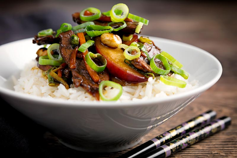 Landscape image of a duck with plums recipe with spring onions and carrots served in a white bowl with white rice