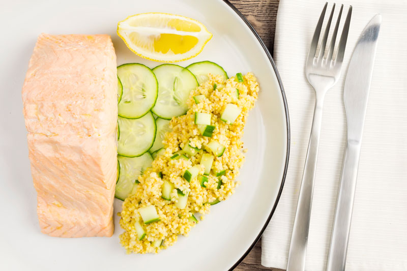 Landscape overhead image of a poached salmon fillet served with cucumber and millet on a white plate with a wedge of lemon