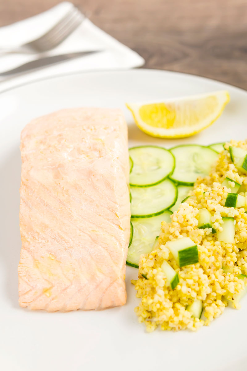 Portrait image of a poached salmon fillet served with cucumber and millet on a white plate with a wedge of lemon
