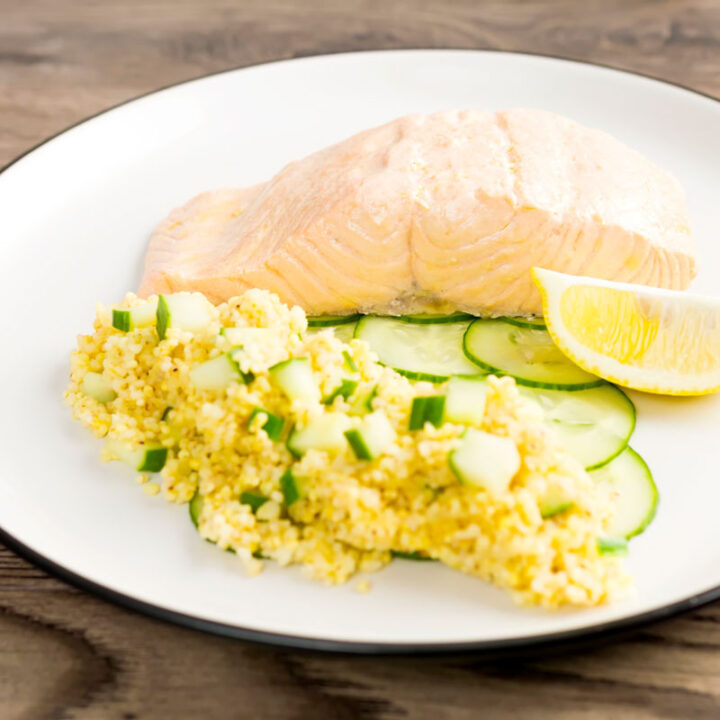 Square image of a poached salmon fillet served with cucumber and millet on a white plate with a wedge of lemon