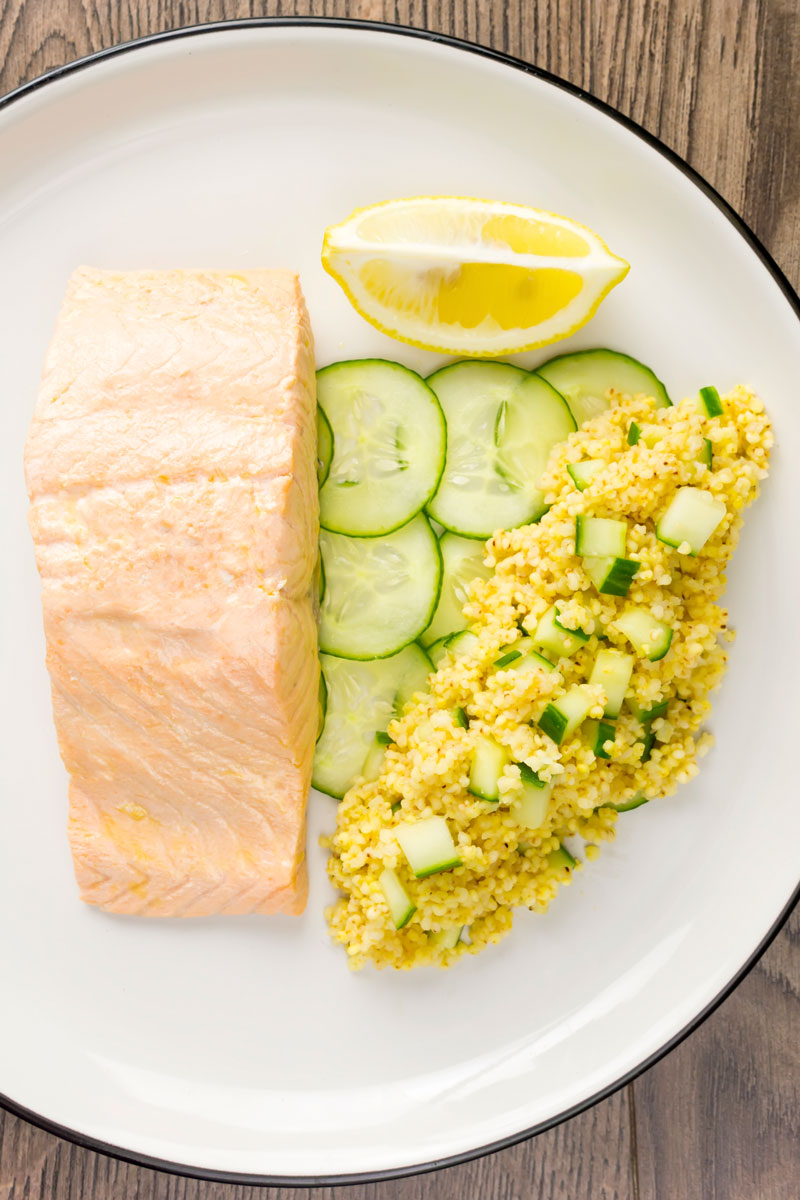 Portrait overhead image of a poached salmon fillet served with cucumber and millet on a white plate with a wedge of lemon