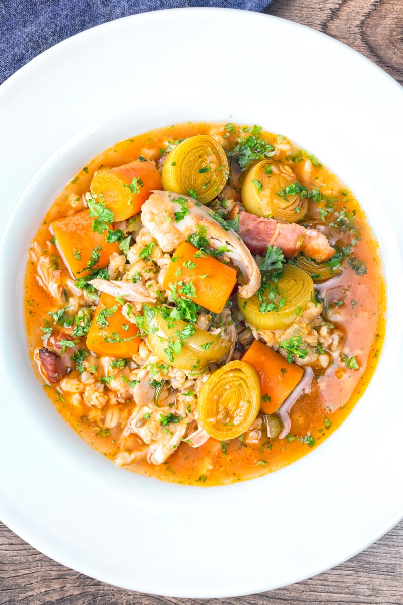 Portrait overhead image of a shredded rabbit stew with pearl barley, carrots and leeks served in a white bowl