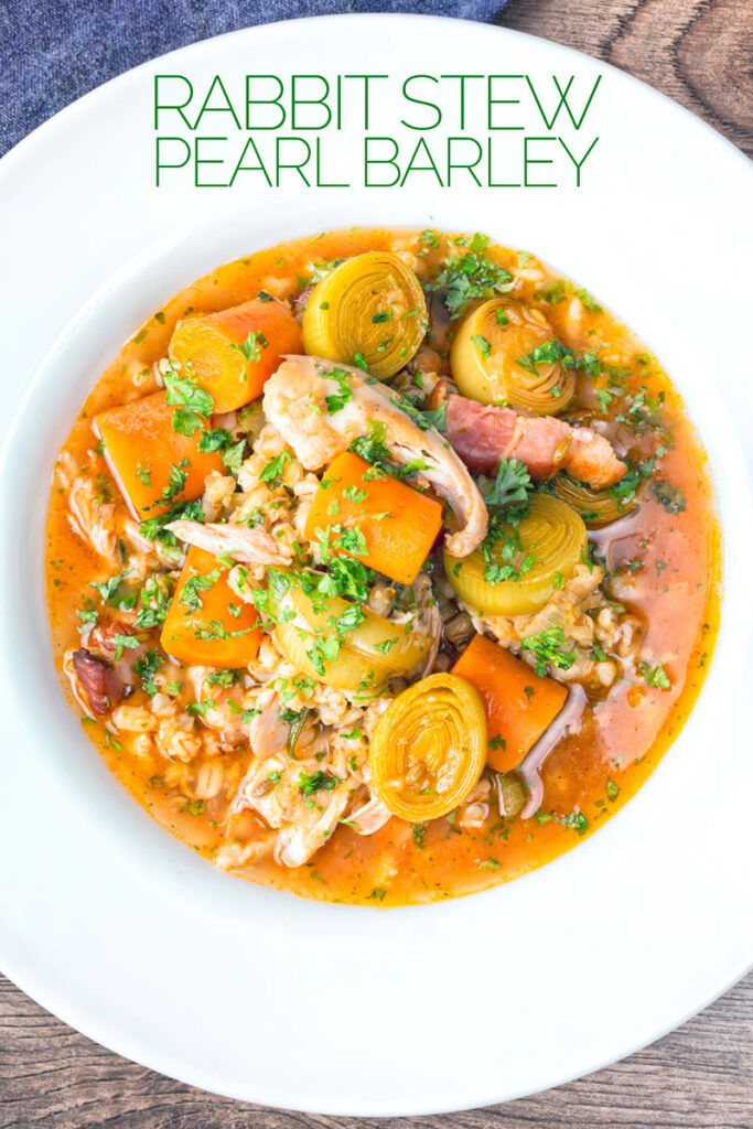 Portrait overhead image of a shredded rabbit stew with pearl barley, carrots and leeks served in a white bowl with text overlay