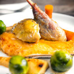 Close up portrait image of a roast guinea fowl leg served on a white plate with out of focus vegetables with text overlay