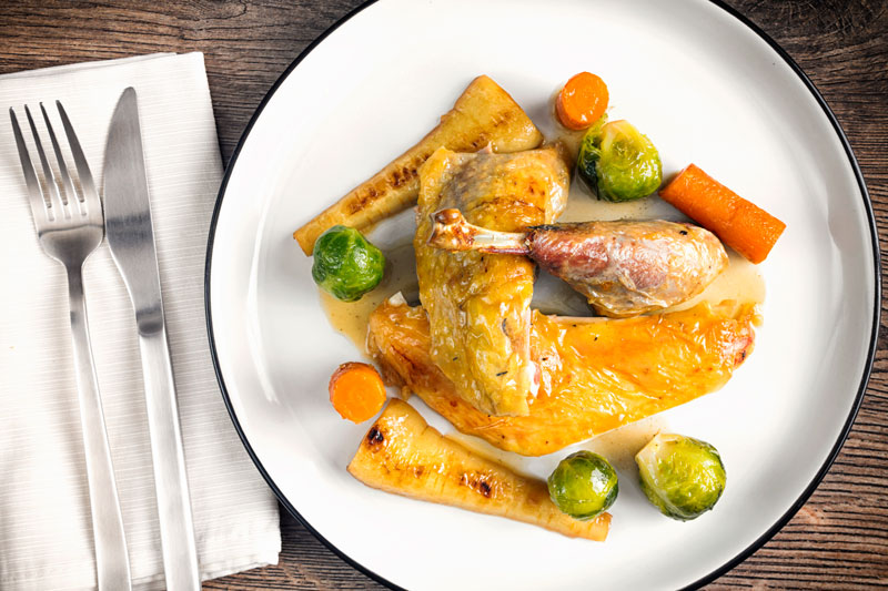 Landscape overhead image of a roast guinea fowl leg served on a white plate with honey glazed vegetables