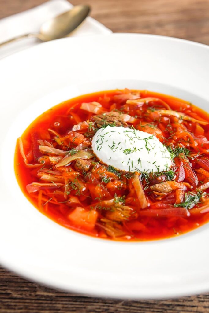 Portrait image of a Russian Borscht Soup served in a white bowl with sour cream and dill