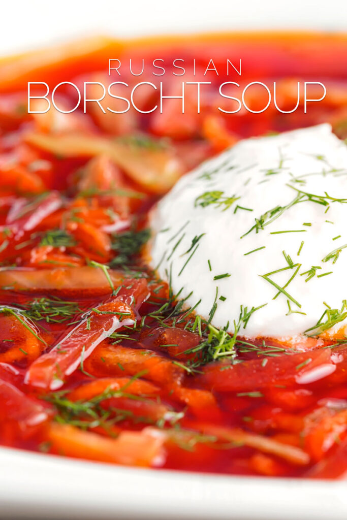 Close up portrait image of a Russian Borscht Soup served in a white bowl with sour cream and dill with text overlay