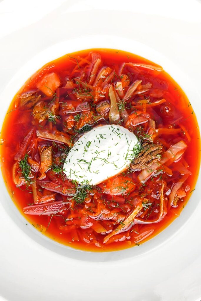 Portrait overhead image of a Russian Borscht Soup served in a white bowl with sour cream and dill