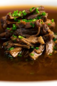 Close up portrait image of a classic British style oxtail soup with shredded beef and snipped chives
