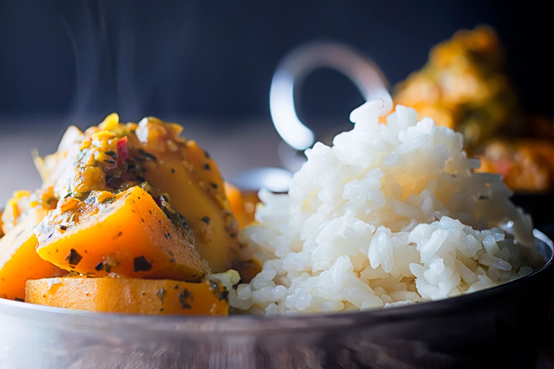 Landscape close up image of a pumpkin curry served with white rice